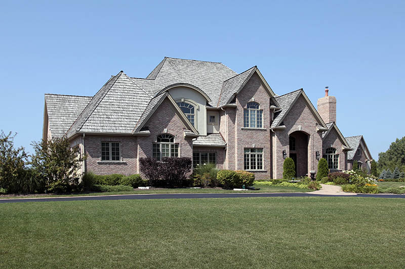 Large brick suburban home with arched entry
